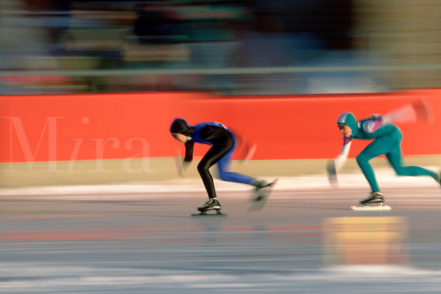 Two skaters skate around an indoor track during a speed skating competition. competitive sports.
