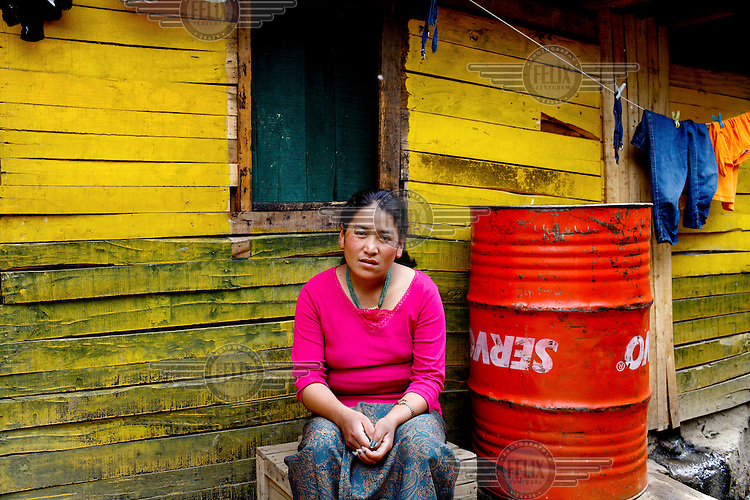 A woman sits outside the window of her house in a slum.