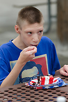 Michael McCollum<br /> 8/2/18<br /> Ryan tries out the cake at the reveal ceremony where it was announced to 13 year old Ryan Overman of west Knoxville that The Wish Connection is granting Ryan&rsquo;s wish to go to Washington DC and visit the White House at Carl Cowan Park, 10058 S Northshore Dr, Knoxville, TN&nbsp;, Thursday, August 2, 2018 at 5:45pm. Approximately 50-60 people attended, including the Overman family, friends, and AT&amp;T Employees. The Bearden High School Cadets also attended and lead the pledge of allegiance.<br /> &nbsp;The AT&amp;T Wish Connection is going to send Ryan, his family, and his service dog to Washington DC and while they are gone, the group of volunteers will be doing a makeover on his bedroom and turn it into the &quot;Oval Office&quot; at the White House.<br /> Ryan was born two weeks prematurely on May 13, 2005.&nbsp; During the pregnancy he was classified as high risk due to a measured lack of growth and, after a brief stay in the hospital, he came home weighing only 4 lbs 5 oz.&nbsp; His development was much slower compared to his peers, such as not learning to walk until he was well over a year old, and he was much smaller. The Overman family worked with Tennessee Early Intervention Services (TEIS) when Ryan was about one year old and with their help they were able to get Ryan enrolled through TEIS to receive Occupational, Physical, and Speech Therapy.&nbsp; When Ryan turned three he transitioned from TEIS to the Knox County Early Intervention Program and began attending a special school to continue his therapies until he was old enough to enroll at Cedar Bluff Elementary and now is at Cedar Bluff Middle School. In 2016, Ryan was diagnosed to have retinitis pigmentosa, a degenerative disease of the retinas that under the best of circumstances causes severe tunnel vision, but more commonly results in complete blindness.<br /> &nbsp;Despite the physical difficulties that Ryan has had to endure over the last thirteen years, he continually brightens the lives of those around him.&nbsp; If someone is hurting