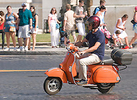 A Vespa PX scooter, painted in flashing orange.