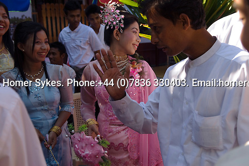 Sittwe. Northern Rakhaing State. Myanmar (Burma) 2008. Wedding party. The bride in traditional costume. Best man tries to creat patway for the groom to leave the wedding party.