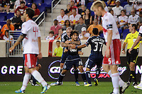 Davide Chiumiento (20) of the Vancouver Whitecaps celebrates scoring with teammates during a Major League Soccer (MLS) match at Red Bull Arena in Harrison, NJ, on September 10, 2011.