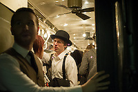 New Yorkers, tourists and subway buffs, some in period garb, travel on a vintage MTA Nostalgia Train Christmas season ride on Sunday, December 16, 2012. The straps, ceiling fans and rattan seats are a far cry from the plastic and air conditioning in modern subway cars. The Metropolitan Transit Authority has several of these trains for the various subway lines which they put into use for special occasions. The trains normally reside in the New York City Transit Museum in downtown Brooklyn where they can be visited every day.  © Frances M. Roberts)
