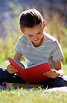 Young girl (8 years old) reading a book sitting down on a blanket at a picnic summer reading Lake Pleasant Bothell Washington State USA MR