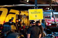 Jul 12, 2020; Clermont, Indiana, USA; Detailed view of a sign requesting face masks be worn in the pit area of NHRA funny car driver Cruz Pedregon during the E3 Spark Plugs Nationals at Lucas Oil Raceway. This is the first race back for NHRA since the start of the COVID-19 global pandemic. Mandatory Credit: Mark J. Rebilas-USA TODAY Sports