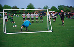 AF5GM6 Children's football tournament. View of goalkeeper from behind the net. Penalty shoot out.