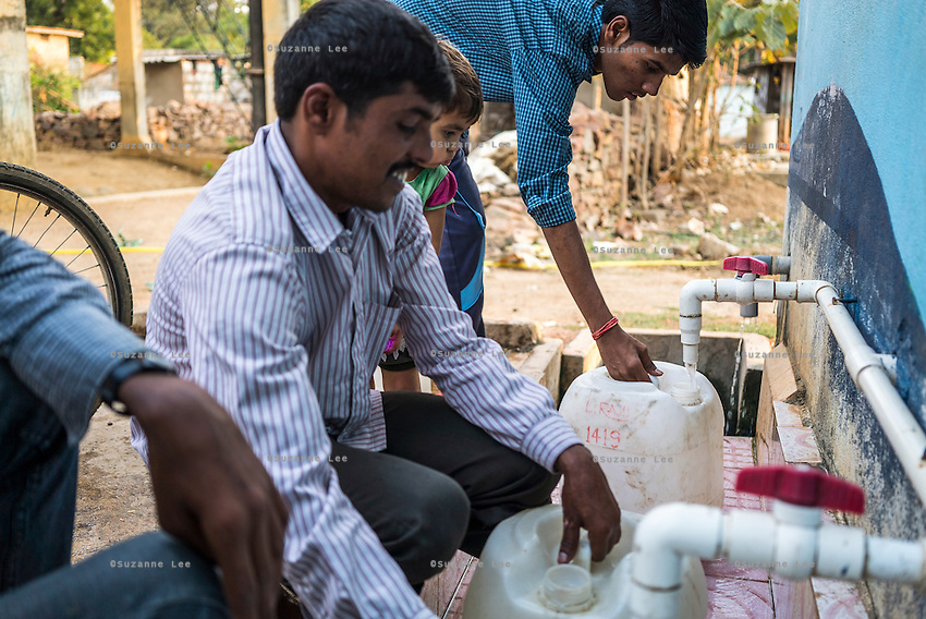 Customers gather at the iJal water station to buy drinking water in Gorikathapalli, a remote village in Warangal, Telangana, India, on 22nd March 2015. Safe Water Network works with local communities that live beyond the water pipeline to establish sustainable and reliable water treatment stations within their villages to provide potable and safe water to the communities at a nominal cost. Photo by Suzanne Lee/Panos Pictures for Safe Water Network