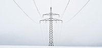 Electircal power lines on cloudy winter day cross snow covered field, Oberpfalz, Bavaria, Germany