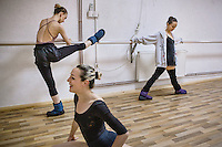 Three members of the new generation of The Kosovo Ballet get warmed-up before rehearsal in the training room of Kosovo Ballet, Kosovo National Theater, Pristina. Most of the troupe members work full time for the ballet. But in post-war Kosovo, where living cost is high and unemployment are widespread, they only can earn as little as 250-350 euro per month which is proved difficult.