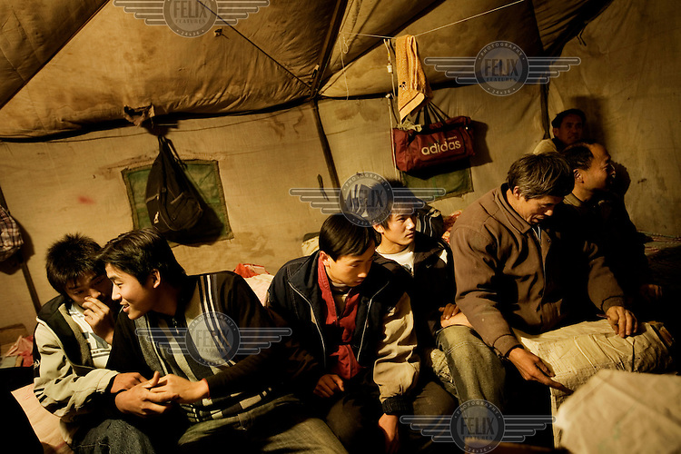 Migrant workers sit on their bed in a dormitory where about ten to fifteen workers sleep. .