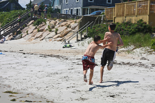 Boys playing tag on the beach.