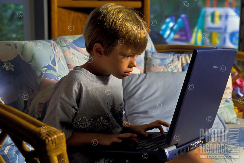 A young boy concentrates as he works at a laptop computer.