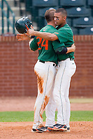 Harold Martinez #9 (right) of the Miami Hurricanes hugs teammate Yasmani Grandal #24 after scoring on a grand slam by Zeke DeVoss #7 (not pictured) against the Boston College Eagles at the 2010 ACC Baseball Tournament at NewBridge Bank Park May 27, 2010, in Greensboro, North Carolina.  The Eagles defeated the Hurricanes 12-10 in 10 innings.  Photo by Brian Westerholt / Four Seam Images