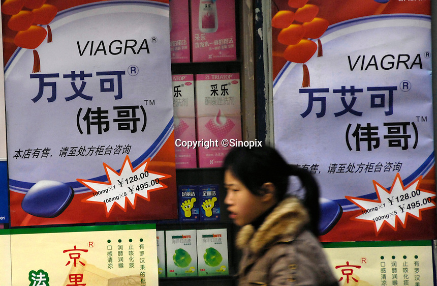 A Chinese girl walks past advertisemts of Pfizer's anti-impotence drug Viagra in Nanchang, jiangxi province, China..