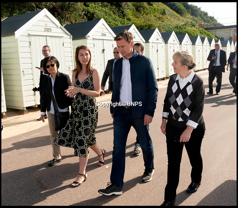 BNPS.co.uk (01202 558833)Pic:   RogerArbon/BNPS<br /> <br /> Jeremy Hunt walks past the beach huts in Bournemouth this morning.  The PM candidate took a few minutes to speak to local people too.