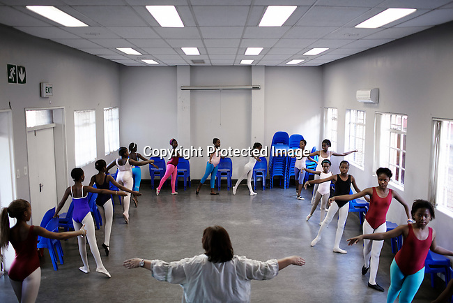 SOWETO, SOUTH AFRICA MAY 3: Ballet students practice during a class on May 3, 2013 in Orlando section of Soweto, South Africa. South African Mzansi Ballet runs a project in Soweto teaching young boys and girls classical ballet. Many of the young people growing up have many more opportunities than their parents. Soweto is today a mix of old housing and newly constructed townhouses. A new hungry black middle-class is growing steadily. Many residents work in Johannesburg but the last years many shopping malls have been built, and people are starting to spend their money in Soweto. (Photo by: Per-Anders Pettersson)