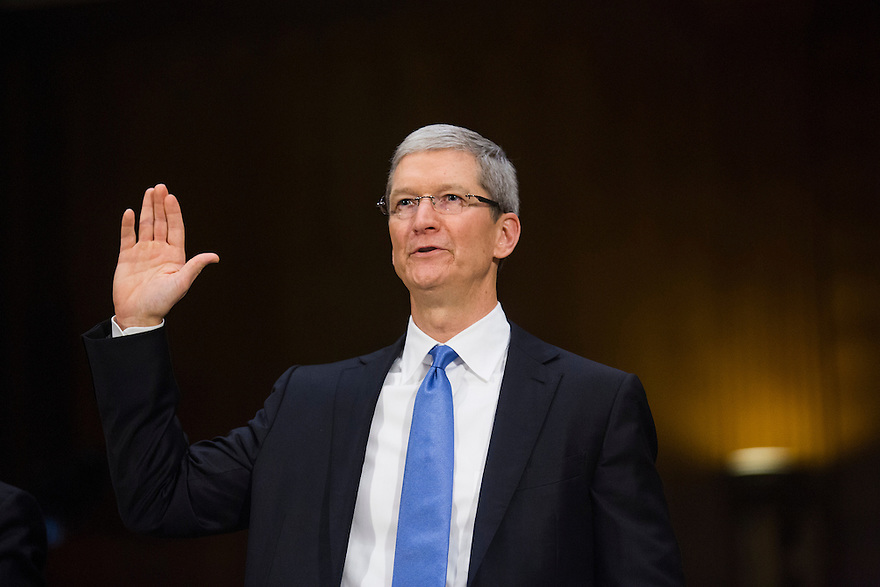 Apple CEO Tim Cook takes the oath before testifying at a Senate homeland security and governmental affairs investigations subcommittee hearing on offshore profit shifting and the U.S. tax code, on Capitol Hill in Washington. Cook defended the company's tax record during a Senate hearing where lawmakers said the maker of iPads, iPods and Mac computers kept billions of dollars in profits in Irish subsidiaries to avoid U.S. taxes.