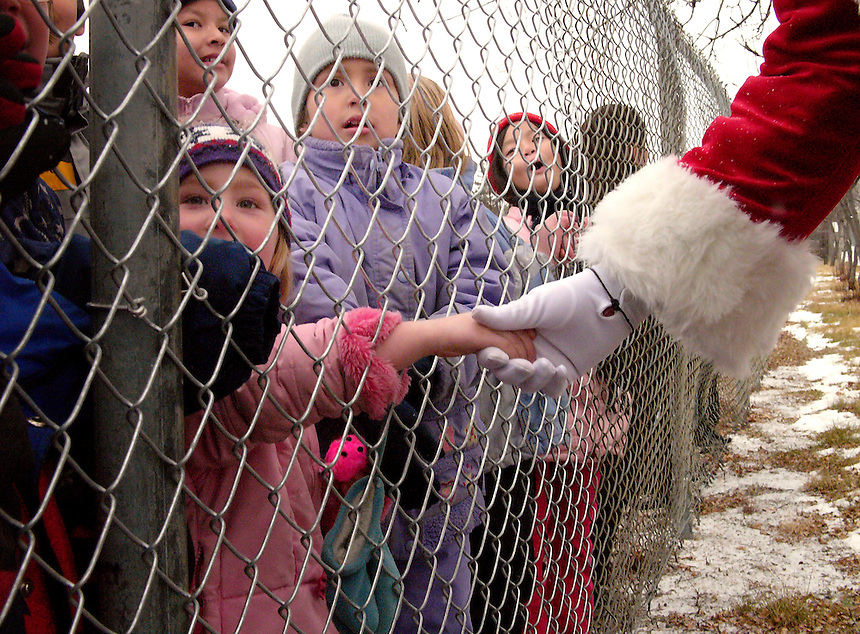 Students from Herchmer School rush to the edge of their playground to meet Santa and get a glimpse of a passing parade marking National Children's Day. MARK TAYLOR GALLERY