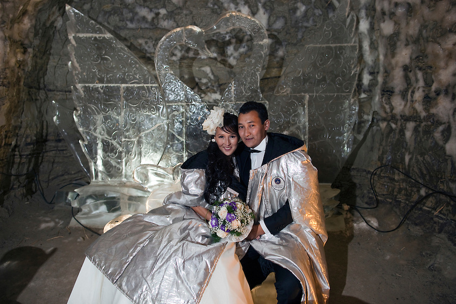 Yakutsk, Yakutia, Russia, 19/08/2011..Newly-weds Nadezhda and Vasily Fedorov on the Love Couch inside the Permafrost Kingdom, an underground tourist attraction inspired by the extreme cold of Yakutia. The 150 metre deep complex of tunnels in the Russian permafrost are decorated with ice sculptures, a wolf-fur covered throne, an office complete with the coolest computer and telephone, a children's slide and other ingenious creations - all hewn from blocks of ice.