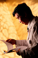 A male practitioner of traditional Chinese medicine (TCR) reviews a medical record.
