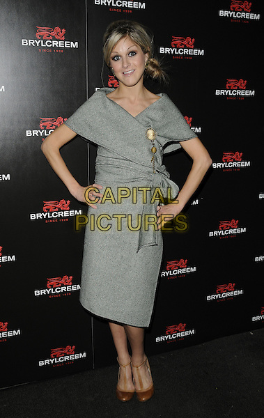 NIKKI GRAHAME .The Brylcreem Ball - launch party, Vendome, London, England. .October 27th, 2010 .full length dress grey gray wool hands on hips wrap brooch brown ankle strap shoes .CAP/CAN.©Can Nguyen/Capital Pictures.