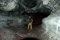 Hiker in one of the large lava tubes from the Hualalai volcano 1801 flow Kailau Kona The Big Island of Hawaii, Hawaii, Pacific Ocean