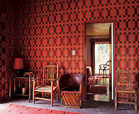 The walls of the master bedroom are covered in sumptous scarlet fabrics, their busy patternation belying the fact the room is actually very simply furnished with rustic wooden chairs and a stone floor