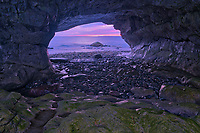View of rocks along the Gulf of St. Lawrence at dusk as seen though the rock arch. Northern Peninsula. <br />