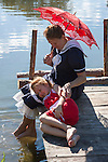 A vintage young mom and child enjoying the summer relaxing on a pier with a red umbrella