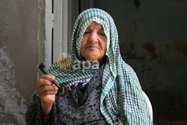 Palestinian refugee Kamleh Kadada, 76, carries the key of her former house, at the al-Shati refugee camp in Gaza City. Hundreds of thousands of Palestinians were uprooted during the 1948 war over Israel's creation, and some 4.5 million Palestinian refugees and their descendants are scattered across the region today. Israel is marking its 60th anniversary today. Israel celebrates its 60th birthday, an anniversary that for the Palestinians, more divided than ever before and hungry for a state of their own, marks a 'catastrophe'.