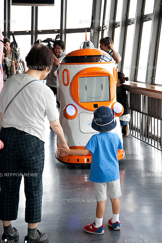 "August 01 2012, Tokyo, Japan - Visitors see the new robot guide ""Tawabo"" at vantage point of Tokyo Tower. Tokyo Tower implemented the new robot guide which name is ""Tawabo"", the first indoor robot guide in Japan. It can speak Japanese, English, Chinese and Korean, it weights 200kg and it is 160cm tall."