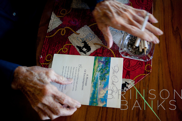 """Will Langdon smokes as he looks at a condolense card from his wife's death in his home in Sun City, Arizona January 9, 2010. Will has lived in Sun City since it opened in 1960. This year is Sun City's 50th anniversary..When he first came to Sun City with his wife the area was surrounded by cotton fields. His house was one of the first built in Sun City. Before he had a wall in his backyard, he and his neighbors would gather on Sundays. """"We would gather and bring all the tables and food out. It was ver nice, but times change and people die,"""" he said..His home is filled with John Wayne and other western memorabilia. """"John Wayne is my heo. He exemplifies what every man should do and be,"""" he said..Will's wife Naomi has since passed away and he is recovering from prostate cancer. He has outlived his friends, as well. """"I'm what you call the last of the Mohicans and I'm holding on."""""""