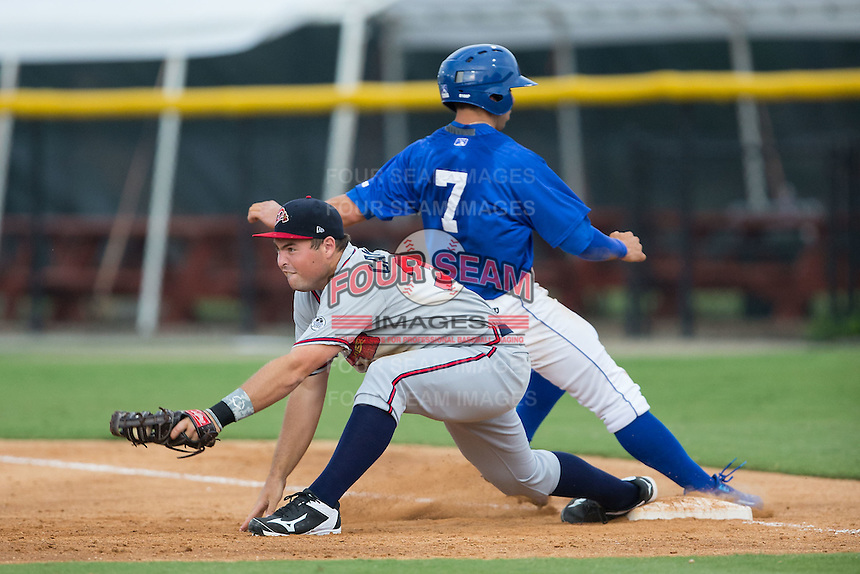 Danville Braves first baseman Jeff Campbell (39) stretches for a throw as Austin Bailey (7) of the Burlington Royals hustles back to the bag at Burlington Athletic Park on July 12, 2015 in Burlington, North Carolina.  The Royals defeated the Braves 9-3. (Brian Westerholt/Four Seam Images)