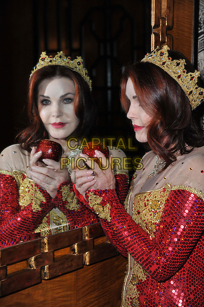 Priscilla Presley.Press launch to star in New Wimbledon Theatre's annual pantomime offering 'Snow White and the Seven Dwarfs' at The Savoy, Strand, London, England..September 26th, 2012.panto costume half length dress side profile mirror reflection hand apple gold red crown sequins sequined  .CAP/BF.©Bob Fidgeon/Capital Pictures.
