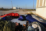 Settler youth sleep early morning outside a caravan house, as settlers gather after rumors were made of a possible eviction of the unauthorized Israeli outpost of Ramat Gilad, West Bank.