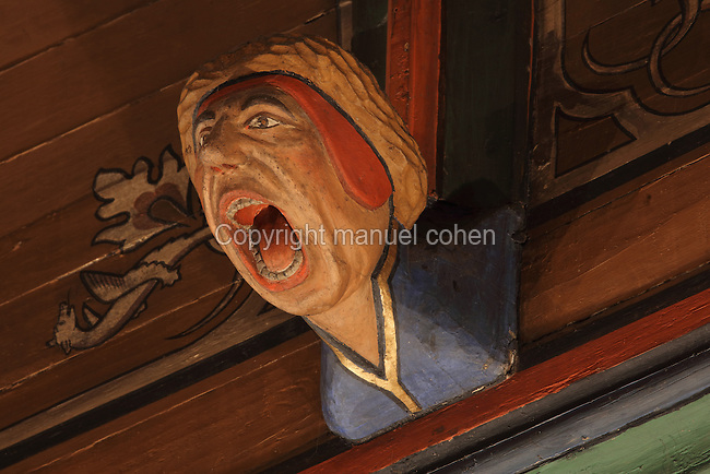 Carved and painted roof bracket with man shouting, architectural detail of the painted wooden ceiling in the shape of a boat's hull, in the Salle des Povres or Room of the Poor, almost 50m long, in Les Hospices de Beaune, or Hotel-Dieu de Beaune, a charitable almshouse and hospital for the poor, built 1443-57 by Flemish architect Jacques Wiscrer, and founded by Nicolas Rolin, chancellor of Burgundy, and his wife Guigone de Salins, in Beaune, Cote d'Or, Burgundy, France. The hospital was run by the nuns of the order of Les Soeurs Hospitalieres de Beaune, and remained a hospital until the 1970s. The building now houses the Musee de l'Histoire de la Medecine, or Museum of the History of Medicine, and is listed as a historic monument. Picture by Manuel Cohen