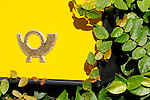 Detail of a bright yellow mailbox with a gold mail/post office symbol in Loveno, a small town on Lake Como, Italy.