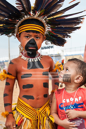 A small Brazilian boy with a face paint design on his cheek looks up at an indigenous Bororo boy at the International Indigenous Games in Brazil. 27th October 2015