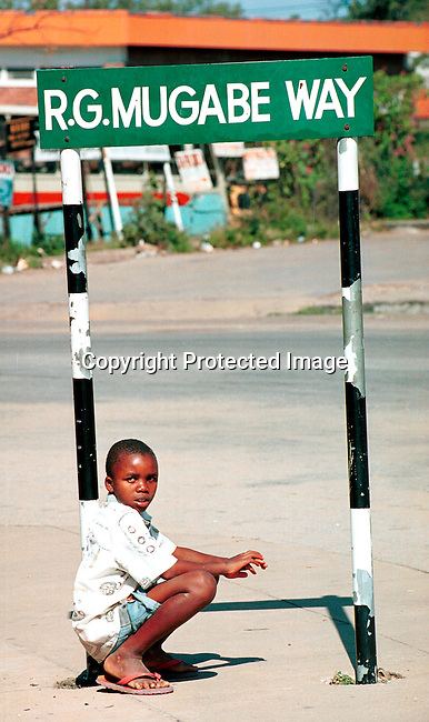 DICOZIM00012 Zimbabwe. A boy hanging out at a street Robert Mugabe street sign, in Harare, Zimbabwe a day before the Parlamentary election on June 24-25, 2000. .©Per-Anders Pettersson/iAfrika Photos