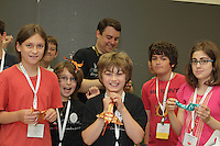 Nathan Ascher (back center) teaches a complex origami dragon design by Diego Fernando Becerra Ramirez to a clas at OrigamiUSA 2013