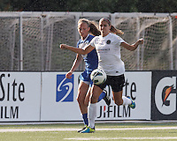 Portland Thorns FC forward Alex Morgan (13) brings the ball forward as Boston Breakers defender Julie King (8) defends. In a National Women's Soccer League (NWSL) match, Portland Thorns FC (white/black) defeated Boston Breakers (blue), 2-1, at Dilboy Stadium on July 21, 2013.