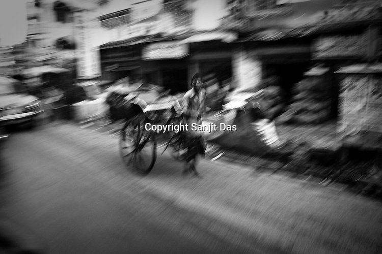 A rickshaw puller takes customers through the traffic in Calcutta, India.