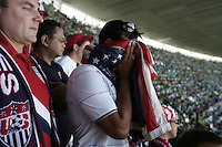 United States Men's National team fans holds an American flag to his face at Azteca stadium. The United States Men's National Team played Mexico in a CONCACAF World Cup Qualifier match at Azteca Stadium in, Mexico City, Mexico on Wednesday, August 12, 2009.