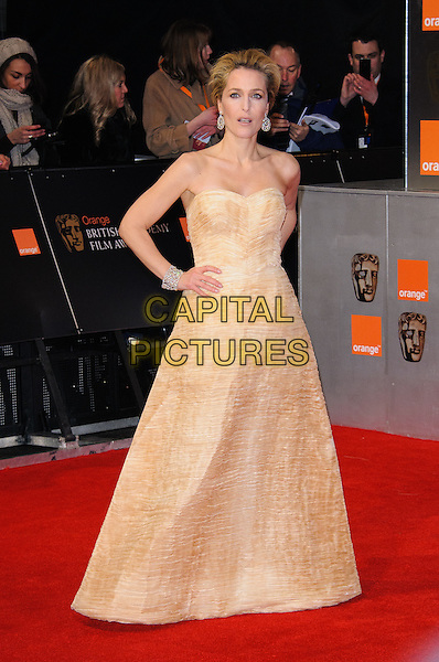Gillian Anderson.The Orange British Academy Film Awards ( BAFTA ), Royal Opera House, Bow St., London, England..February 12th, 2012.baftas full length yellow strapless dress hands on hips.CAP/CJ.©Chris Joseph/Capital Pictures.