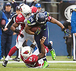 Seattle Seahawks running back Marshawn Lynch (25) is tackled by Arizona Cardinals linebacker Daryl Washington (58) and safety Tony Jefferson (22) during the 2nd quarter at CenturyLink Field in Seattle, Washington on December 22, 2013.   Lynch rushed for 71 yards on 18 carries in the Seahawks 10-17 loss to the Cardinals. .©2013. Jim Bryant Photo. ALL RIGHTS RESERVED.