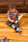 2 year old toddler boy sitting with geometric shapes peg board toy fitting piece onto peg
