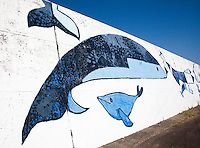 Whale mural decorates the harbour wall from where whale watching tour fishing boats leave.