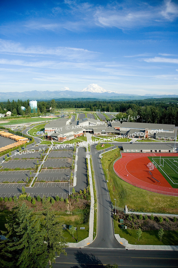 Aerial view of a large, suburban, public high school in Bonney Lake, Washington with yellow school buses defining the edge of the property, a red running track providing contrast for the expansive blue sky, and 14,000 foot Mt. Rainier looming behind