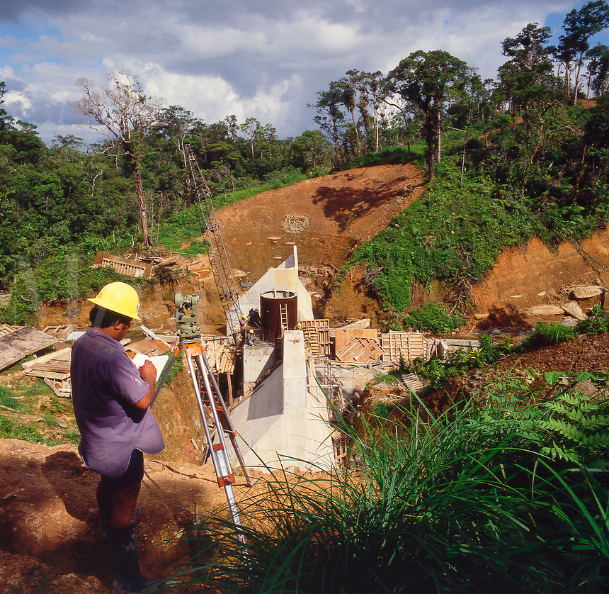 Construction of small reinforced concrete dam for water diversion project. Fiji.  Surveyor checking progress.