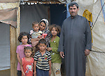 A family that escaped fighting in Aleppo, Syria, poses in the doorway of their shelter in the Aamer al Sanad refugee settlement in Kab Elias, a town in Lebanon's Bekaa Valley which has filled with Syrian refugees. Two of the family's ten children were killed in Syria's civil war. <br /> <br /> Lebanon hosts some 1.5 million refugees from Syria, yet allows no large camps to be established. So refugees have moved into poor neighborhoods or established small informal settlements, such as Aamer al Sanad, in border areas. International Orthodox Christian Charities, a member of the ACT Alliance, provides support for refugees in Kab Elias, including a community clinic.